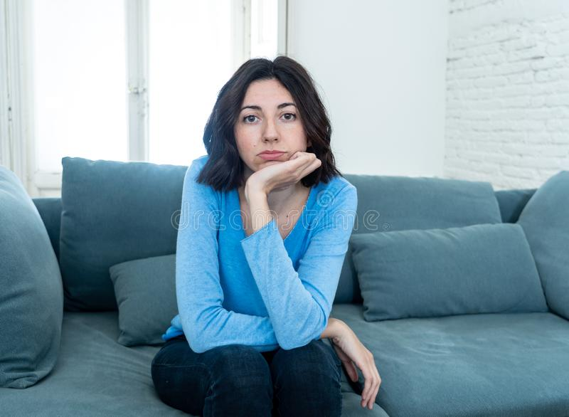Bored woman changing TV channels with remote control. Young upset woman on sofa using control remote zapping bored of bad TV shows and programing . Looking stock image