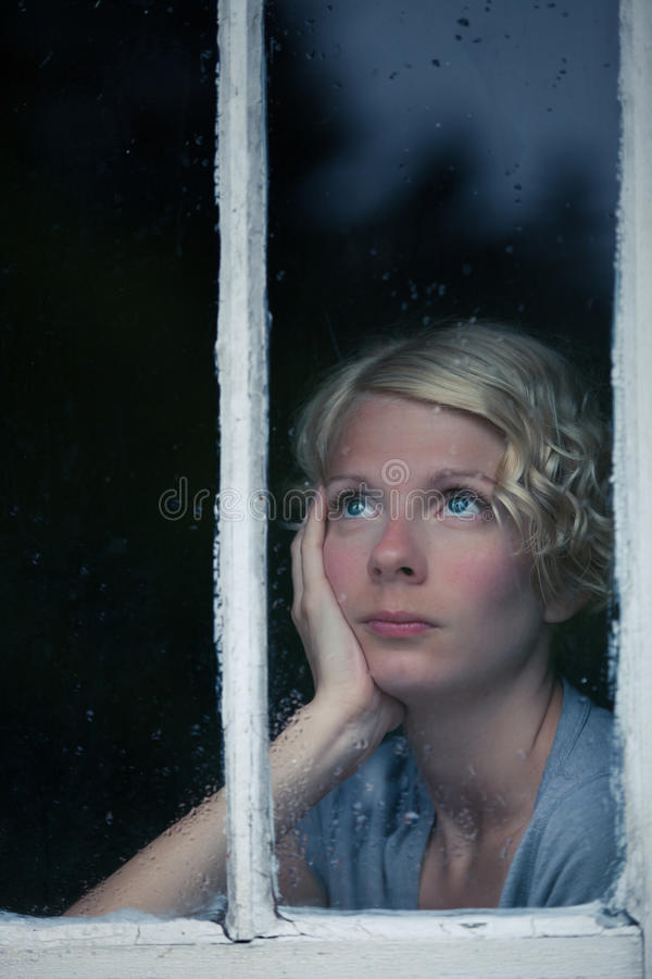 Bored Woman Looking at the Rainy Weather By the Window. Frame royalty free stock images