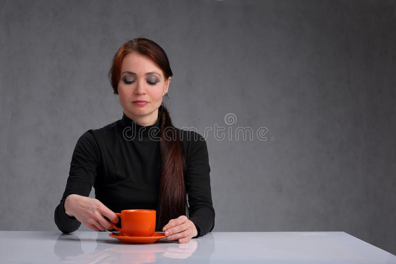 A bored woman with the orange coffee mug. Portrait of a sad, bored woman with an orange Cup of coffee at a white, glossy table royalty free stock images