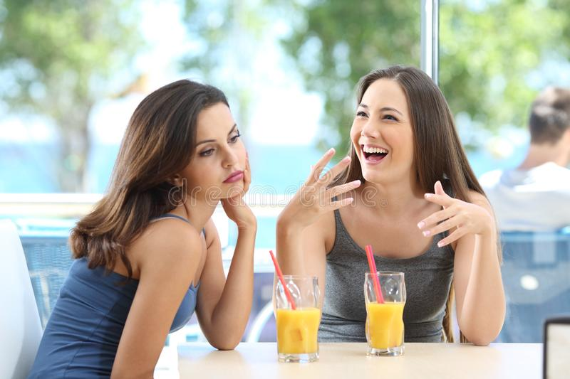 Bored woman suffering a bad conversation from a friend. Bored women suffering a bad conversation from a friend in a coffee shop or hotel on the beach royalty free stock photos