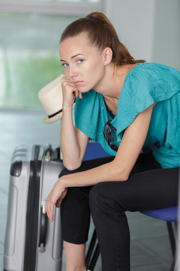 Bored woman waiting with baggage. Bored woman waiting with her baggage royalty free stock photography