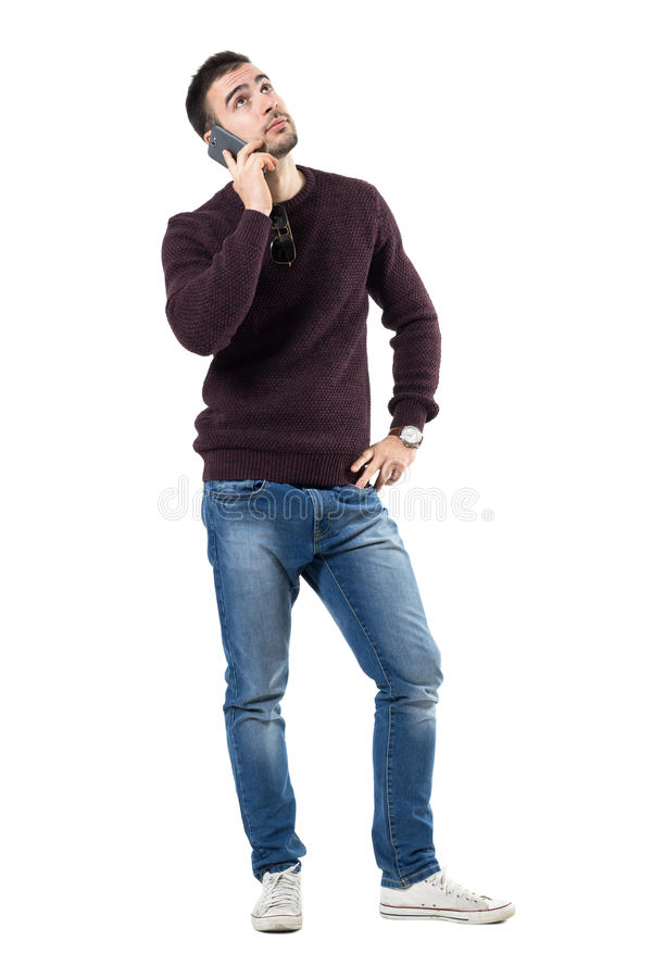 Bored young casual man listening on the phone looking up stock image