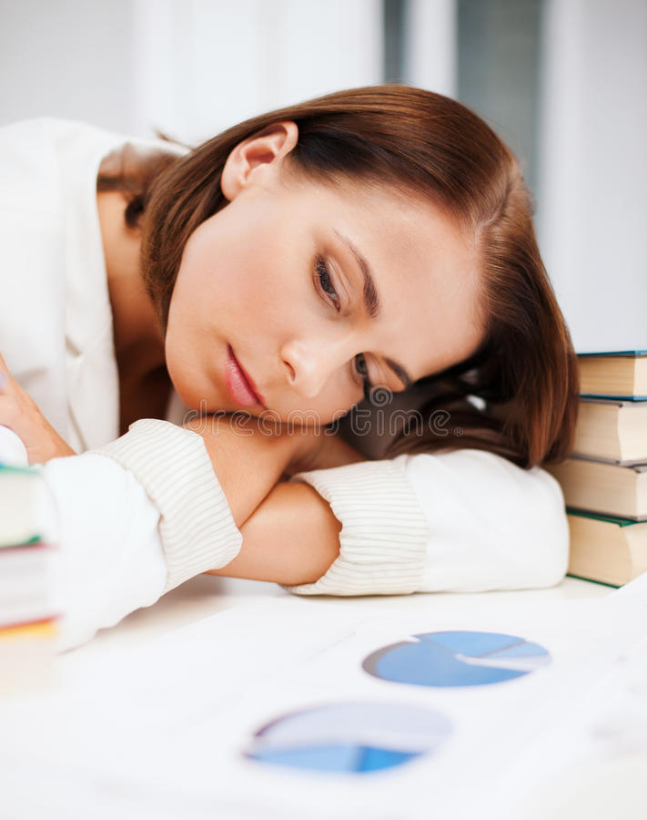 Bored young woman with many books and graphs stock image