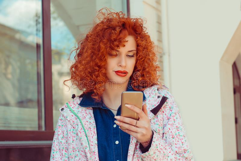 A bored young woman is using a smartphone outdoors in the street. Negative human emotions face expression feeling stock photography