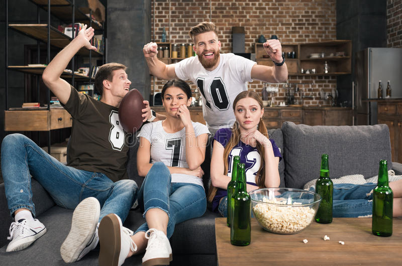 Bored young women sitting near excited men. Supporting favorite football team at home stock images