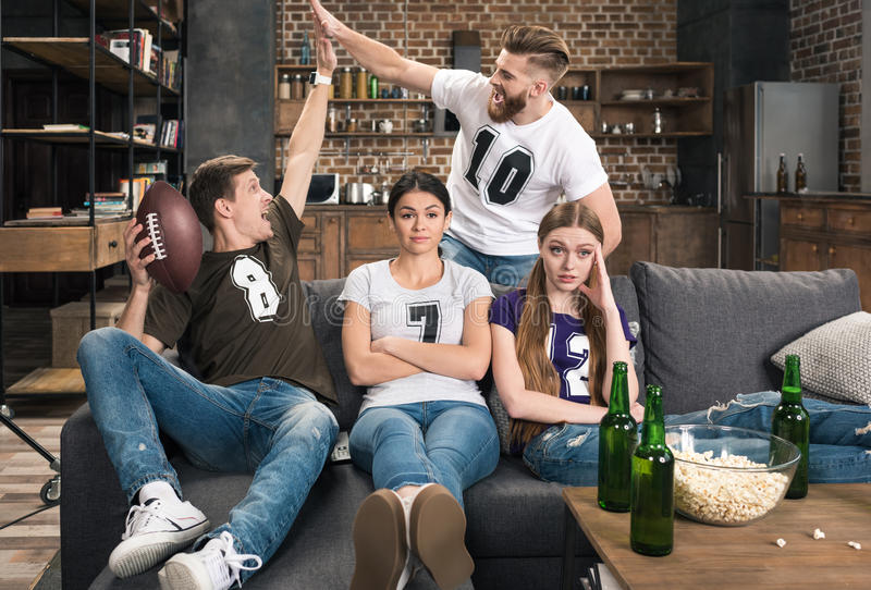 Bored young women sitting near excited men. Supporting favorite football team at home stock photography