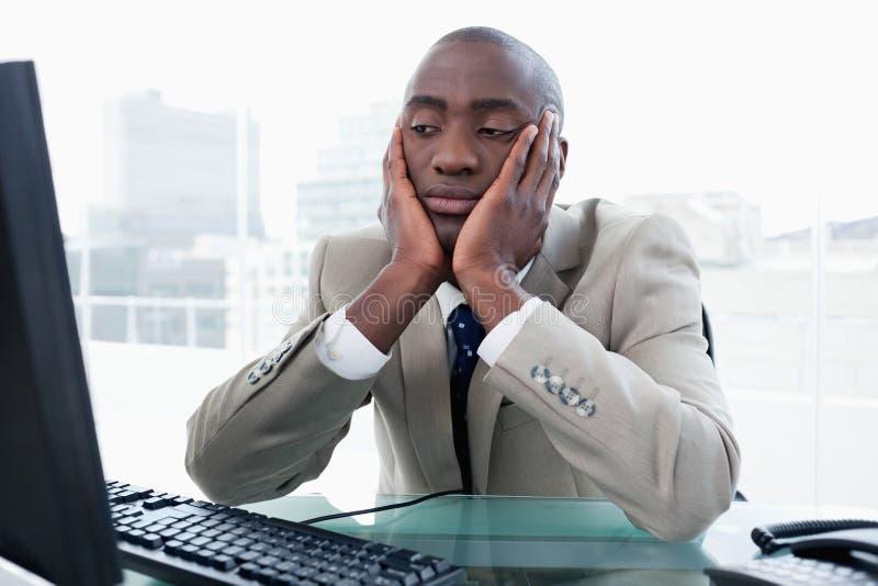 Bored zakenman die zijn computer bekijkt stock afbeeldingen