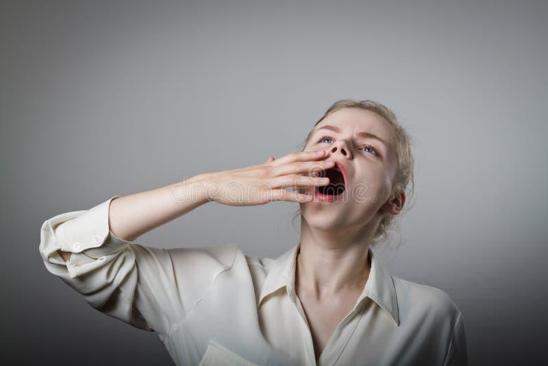 Boredom. Young slim woman is yawning stock photo