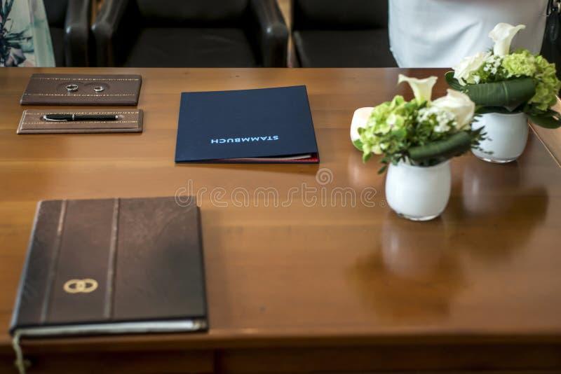Borgerligt tyskt bröllopförbindelseregister Pen Bride Groom Rings och nya härliga blommor för bukett på trätabellen royaltyfri foto