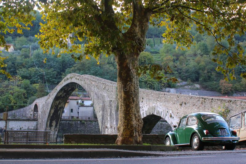 Aged, old and ancient. Medieval bridge, old platan and retro car stock images