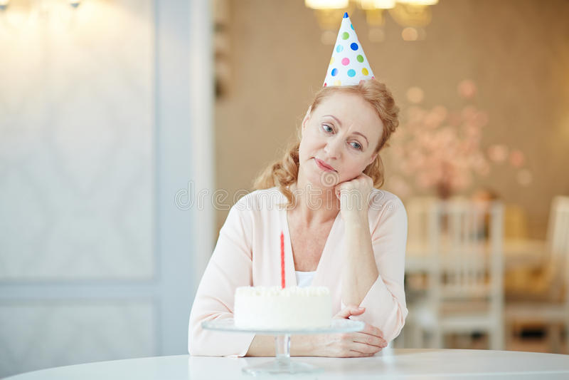 Boring birthday. Unhappy senior woman sitting by table on her birthday stock photos