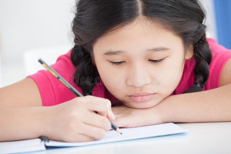 So boring. Close-up of a schoolgirl painting something in the workbook stock photos