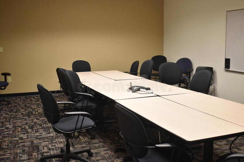 Dull empty conference room in an office building with black chairs and neutral tables and colors royalty free stock images