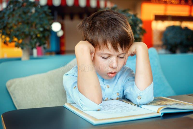 Boring en vermoeid weinig boek van de jongenslezing stock afbeelding