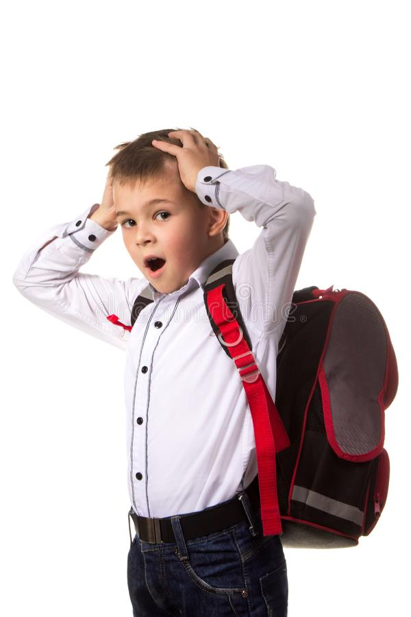 Boring, geeuwende schooljongen die zich met volledige rugzak op de witte achtergrond bevinden Het beginnende gaan naar de school stock fotografie