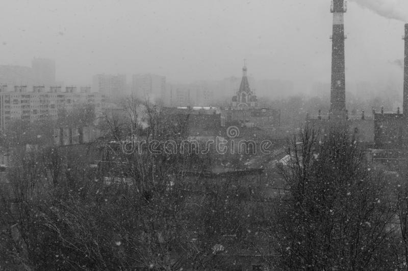 Boring, gloomy black and white cityscape with snow, trees, houses and a church and a factory chimney. This is Russia stock photo