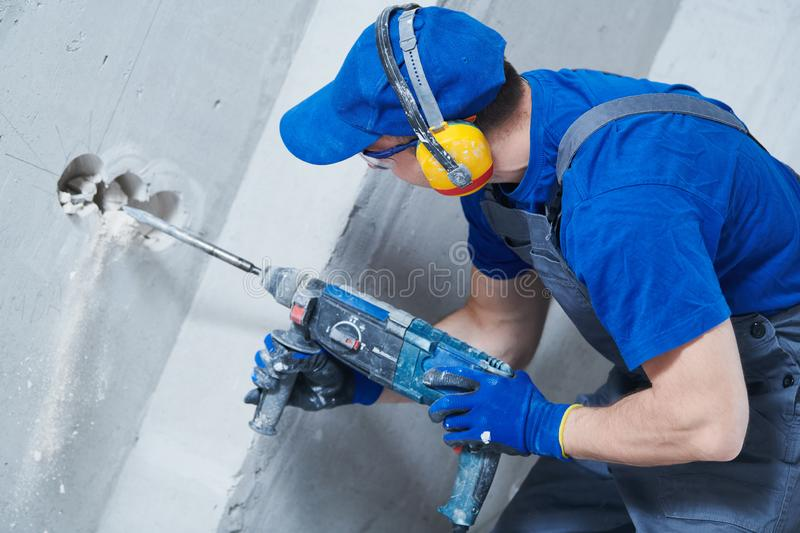 Boring hole for electric outlet by power tool drill. stock images