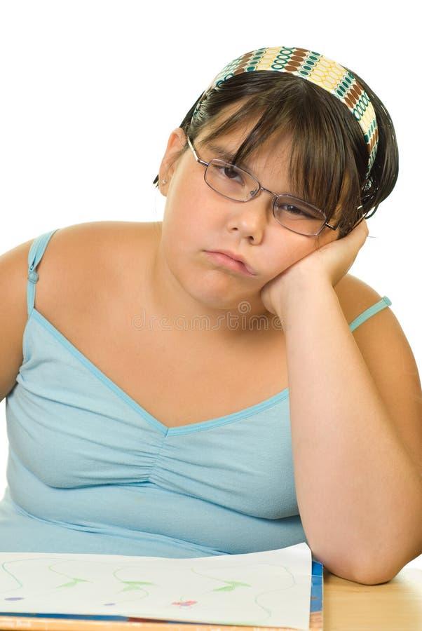 Boring Homework. A young girl looking bored at having to do homework royalty free stock photo