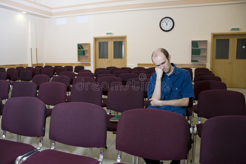Boring lecture. Alone sleeping student in empty au royalty free stock photography