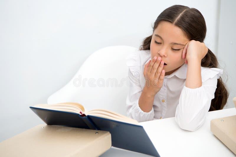 Boring literatuur Het meisjeskind leest boek terwijl lijst witte achtergrond zit Schoolmeisje die en boek bestuderen lezen kid royalty-vrije stock foto