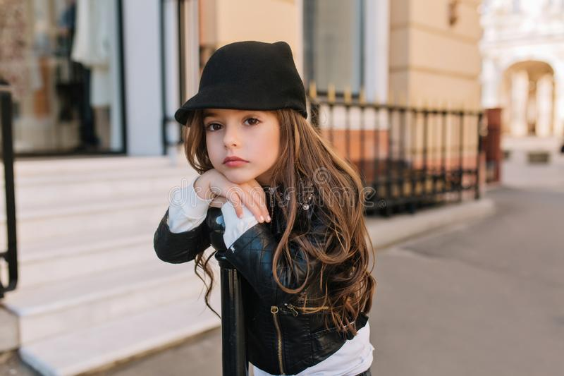 Boring lovely little girl in cute black hat waiting for mother outside in front of beauty saloon. Beautiful long-haired royalty free stock photo