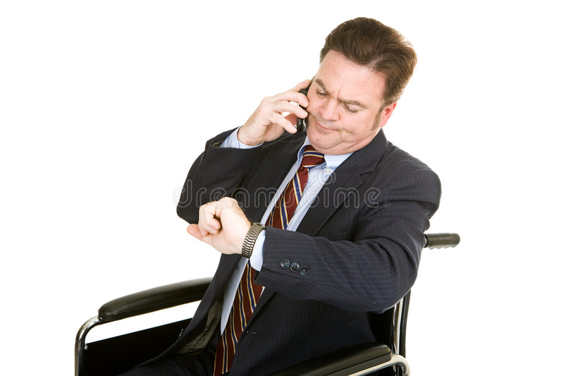 Boring Phone Conversation. Disabled businessman looking at his watch while having a long boring phone conversation. Isolated on white stock images
