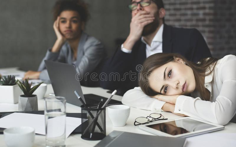 Boring presentation. Young business people looking bored stock images