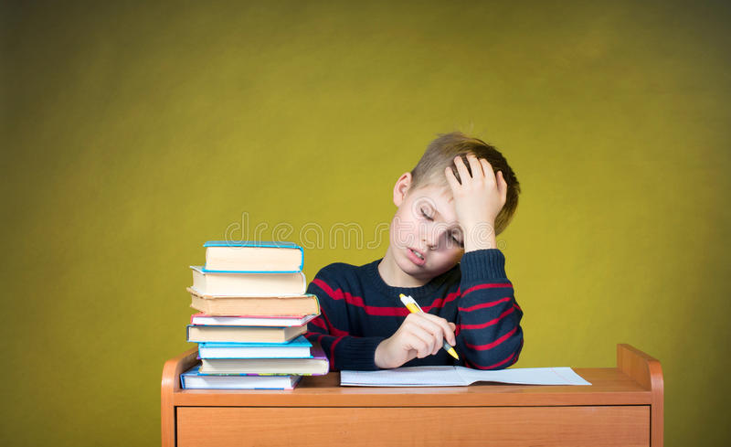 Boring School Studies. Homework. Tired little boy writing. Education concept. stock image