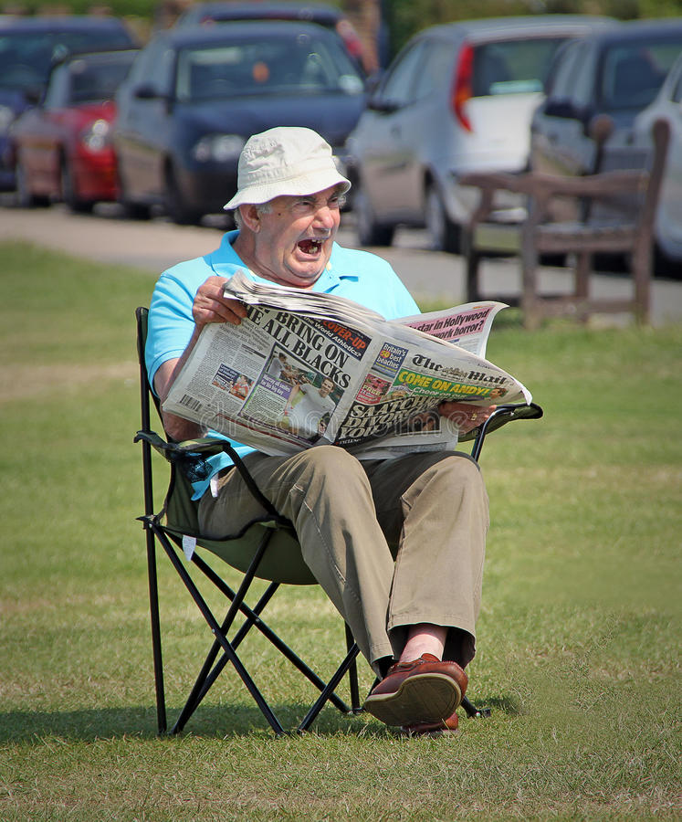 Boring sunday newspaper read. Photo capturing a pensioner yawning as he reads his sunday newspaper in a kent park.nphoto ideal for relaxing,leisure,reading etc royalty free stock photo
