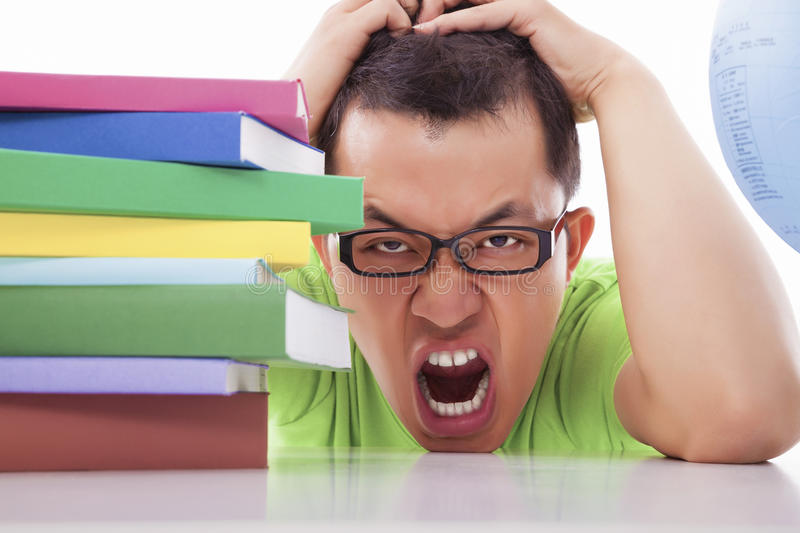 Boring and tired young man with many books. On the desk stock images