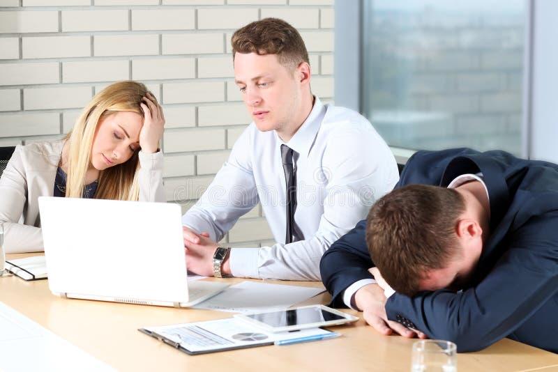 Boring werk Jonge bedrijfsmensen die bored terwijl het zitten samen bij de lijst en weg het kijken kijken royalty-vrije stock foto