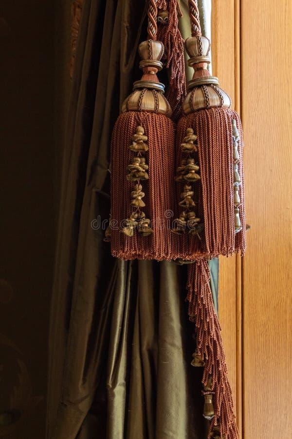 Borlas traseiras, cabos, e guarnição sobre cortinas de seda verdes, fundo de madeira morno do grande laço elaborado da cortina de foto de stock