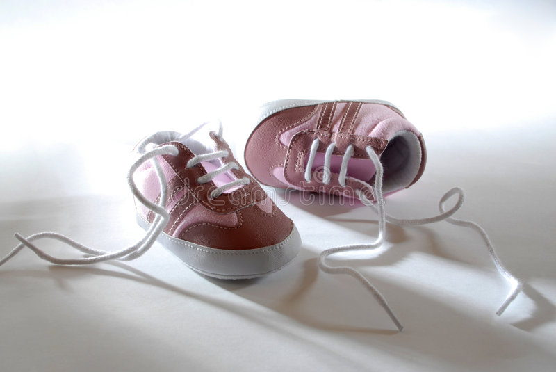 Born. Pink babyshoes in back light stock photos