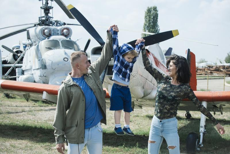 Born to be adventurers. Family on vacation trip. Couple with boy child at helicopter. Helicopter tour and travel. Air. Travel. Enjoying travelling fun. Family stock image