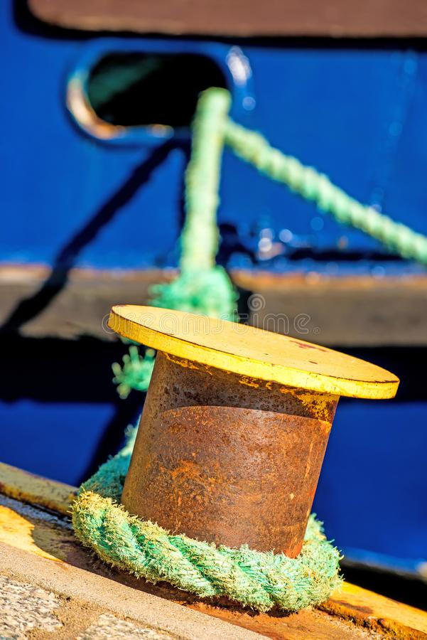 Borne avec la ligne d'amarrage et la coque bleue de bateau images stock