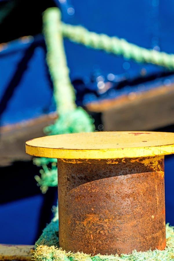 Borne avec la ligne d'amarrage et la coque bleue de bateau photographie stock