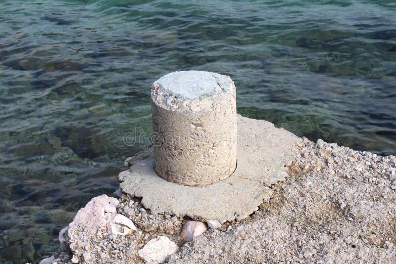 Borne en pierre d'amarrage sur le bord de la jetée concrète à côté de la mer photographie stock libre de droits