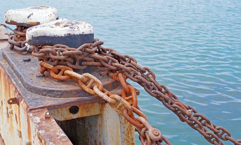 Borne et vieille chaîne rouillée sur le pilier photo libre de droits
