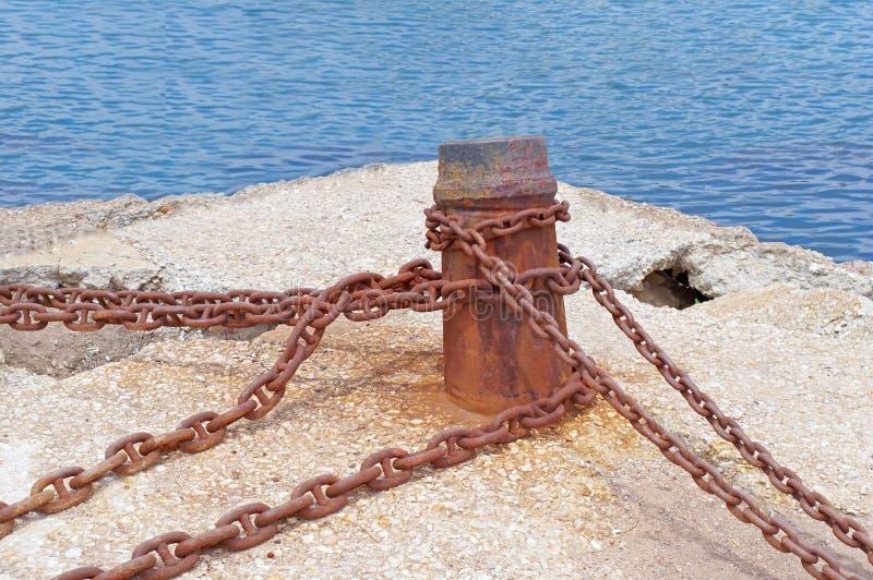 Borne et vieille chaîne rouillée sur le pilier photographie stock
