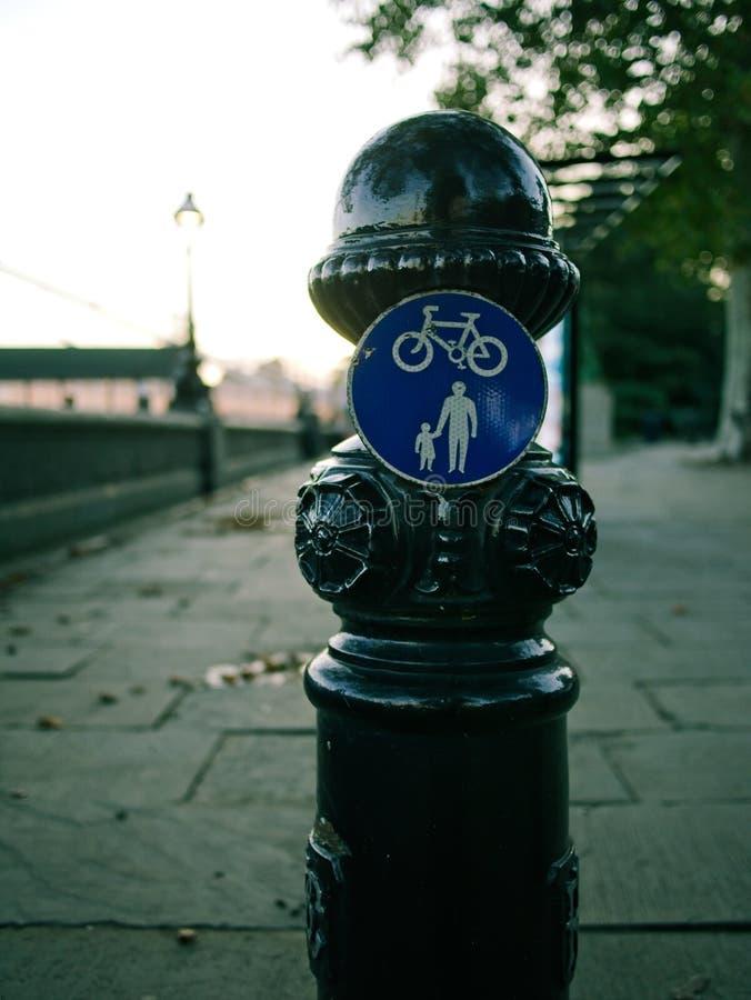 Borne noire britannique traditionnelle avec des panneaux routiers à un trottoir photo stock