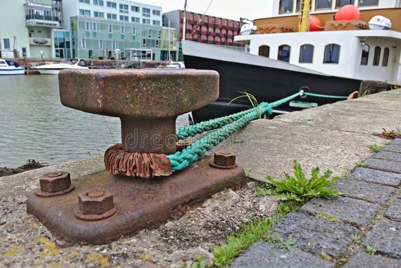 Borne rouillée avec la ligne d'amarrage menant à un bateau à côté du pilier et bâtiments modernes à l'arrière-plan, Bremerhaven p image stock