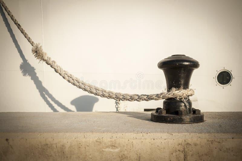 Borne sur un pilier ou un quai, avec la ligne d'amarrage du bateau laided là-dessus photographie stock