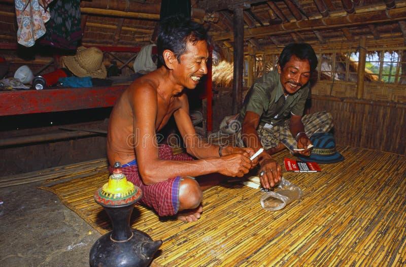 Borneo: Dos Iban Headhunters que se sienta en el bosque largo de la casa bajo la lluvia de Sarawak y que prepara un tubo para fum imagen de archivo