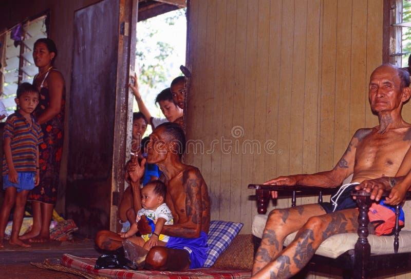 Borneo: Más viejo Iban Headhunter que se sienta en una casa larga típica con la porción de niños alrededor imágenes de archivo libres de regalías