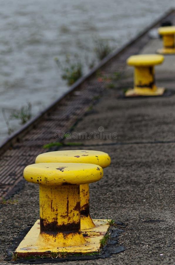 Bornes jaunes sur le quai photographie stock libre de droits