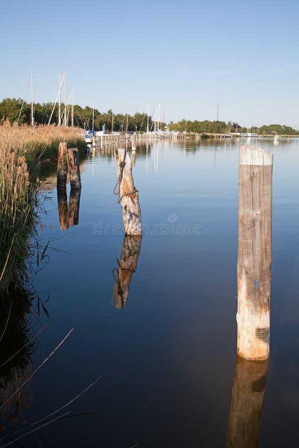 Bornes ou poteaux en bois pr?s d'un pilier et d'une marina avec des bateaux ? voile image stock