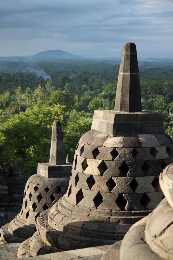 Borobudur bij schemer met rokerige achtergrond van bos en heuvels stock foto's