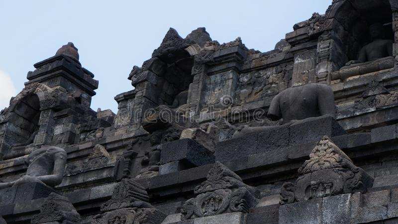 Borobudur Central Java Indonesia 27 Sep, 2019. Buddha statues in front of stone carvings on the side facades of Borobudur Temple.  stock photos