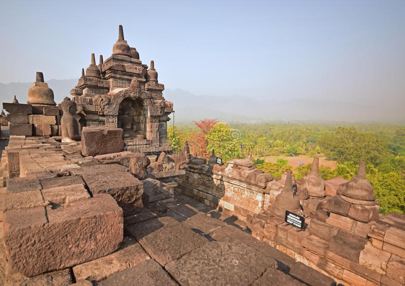 Borobudur during late sunrise with misty feeling among the forest in the background. With Buddha statues and mini stupas. Plenty of mini stupas are seen on the royalty free stock photo