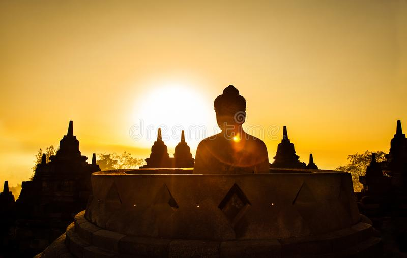 Borobudur Temple at day time Yogyakarta Java Indonesia. Silhouette of Buddha image and some pagoda. The sun is rising in the morning with a big mountain royalty free stock photography